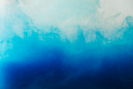 close up view of mixing of blue and turquoise paints splashes  in water