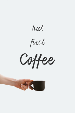 cropped view of hand holding black cup of coffee, isolated on white with But first coffee lettering Banco de Imagens