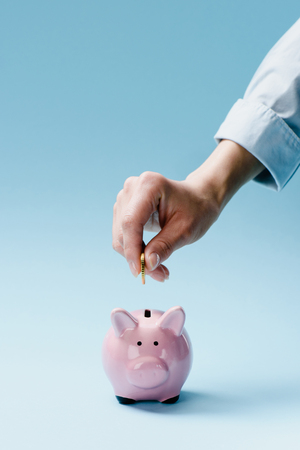 partial view of man putting coin into pink piggy bank isolated on blue