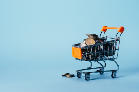 close up view of little shopping trolley full of coins isolated on blue Stock Photo