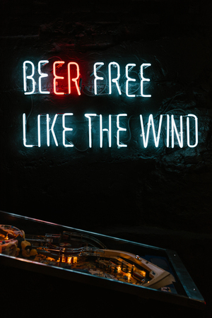 beer free like the wind neon inscription on dark wall and table game in pub
