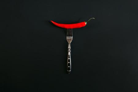 red hot chili pepper on fork on black Stok Fotoğraf