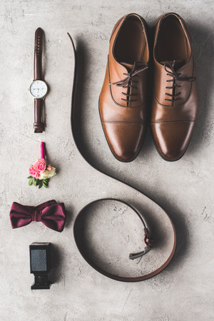 elevated view of male wedding accessories on gray surface