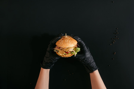 cropped shot of hands in gloves holding delicious burger with turkey, vegetables and caesar dressing on black