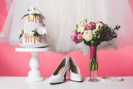 wedding cake on cake stand with white dress and bouquet isolated on pink