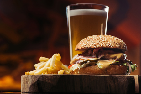 close-up view of tasty burger with turkey, french fries and glass of beer 스톡 콘텐츠