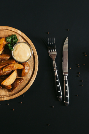 top view of baked potatoes with sauce on wooden board and fork with knife on black Stock fotó