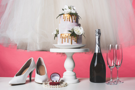 pair of shoes, wedding cake and champagne isolated on pink
