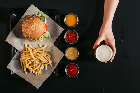 top view of french fries with delicious burger on tray, assorted sauces and hand holding glass of beer on black   Imagens