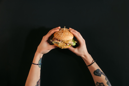 partial top view of hands with tattoos holding tasty burger with turkey and vegetables on black