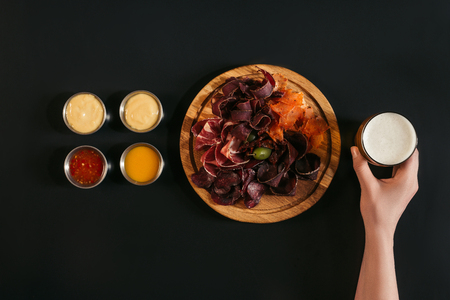 cropped shot of person holding glass of beer and delicious sliced assorted meat on wooden board with various sauces on black
