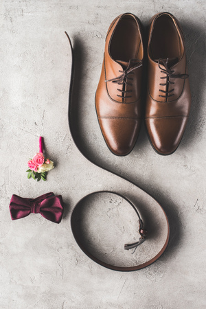 top view of wedding shoes, bow tie, boutonniere and belt on gray surface Stock Photo