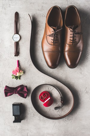 flat lay of male wedding accessories on gray surface Stock Photo