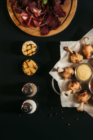 top view of fried tasty chicken wings with sauces, spices, grilled garlic and gourmet assorted craft meat on black  Stock Photo