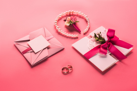 wedding rings, pearl necklace, boutonniere and pink envelopes with invitations on pink surface Stock Photo