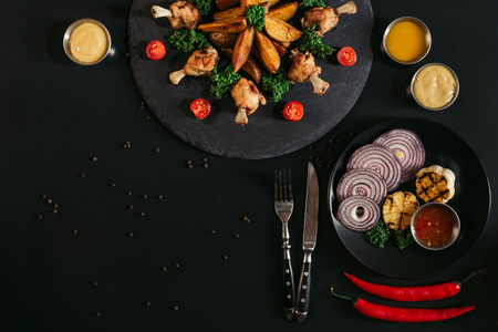 top view of tasty roasted potatoes with chicken, sauces and vegetables on black