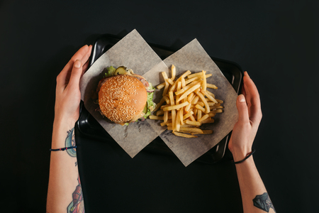 cropped shot of human hands holding tray with delicious burger and french fries on black