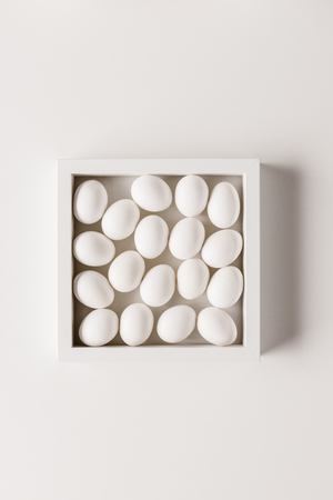 top view of chicken eggs in frame on white background
