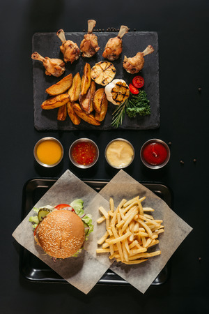 top view of french fries with delicious burger on tray, assorted sauces and slate board with roasted potatoes, grilled vegetables and chicken wings on black Stock Photo