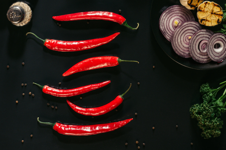 top view of red chili peppers, peppercorns, sliced onion and grilled garlic on black