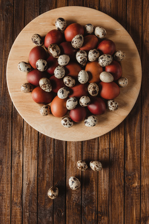 top view of chicken and quail eggs on plate on wood background