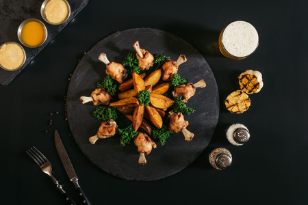 top view of baked potatoes with chicken, glass of beer, grilled garlic and spices on black Banco de Imagens