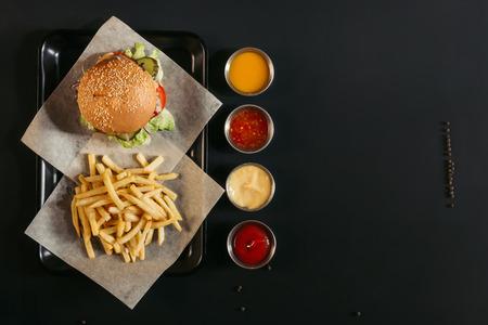 Vista superior de papas fritas con deliciosa hamburguesa en bandeja y salsas variadas en negro