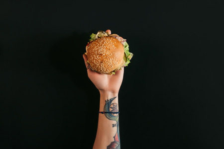 top view of hand with tattoos holding delicious burger with turkey on black