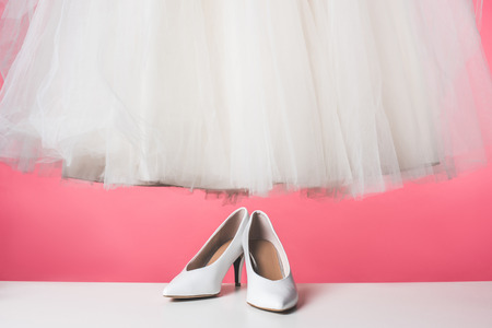 pair of white shoes and wedding dress isolated on pink