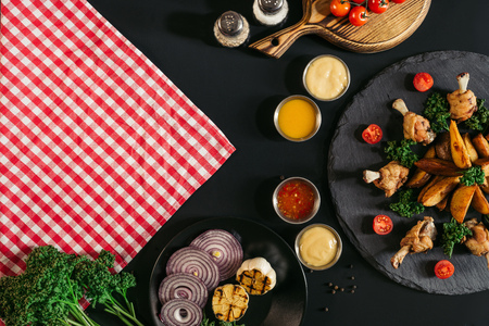 top view of checkered napkin, vegetables, sauces and delicious roasted potatoes with chicken on black  Stock Photo