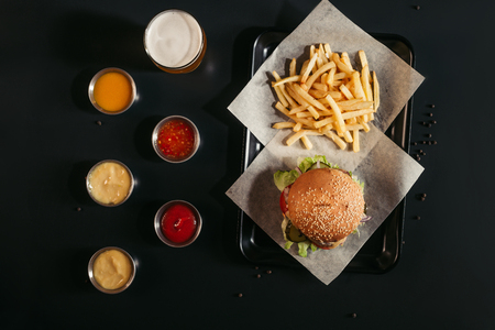 top view of french fries and tasty burger on tray, glass of beer and assorted sauces on black  Imagens