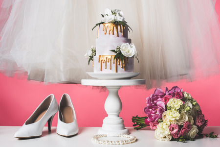 pair of shoes, wedding bouquet and white dress isolated on pink Stock Photo