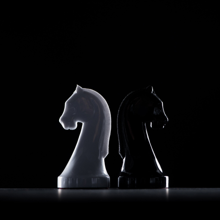 silhouettes of white and black chess knights isolated on black, business concept