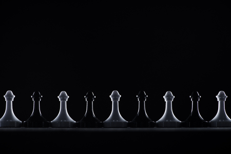 silhouettes of black and white chess pawns isolated on black, business concept Stock Photo