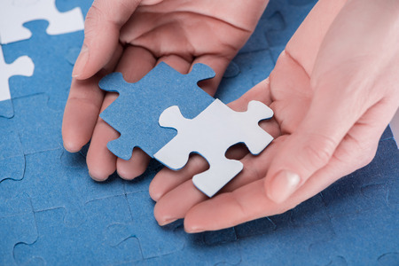 cropped image of businesswoman assembling blue and white puzzles together, business concept Banque d'images - 101299473