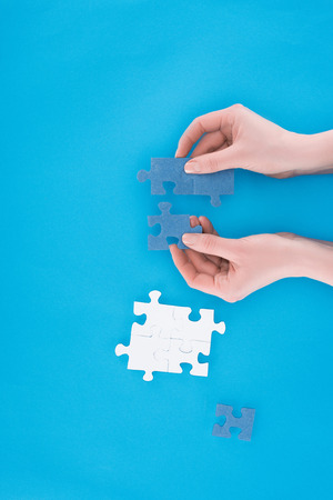 cropped image of businesswoman assembling blue puzzles isolated on blue, business concept Фото со стока