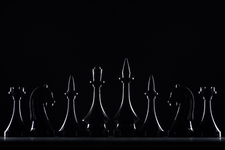 silhouettes of chess figures isolated on black, business concept 스톡 콘텐츠