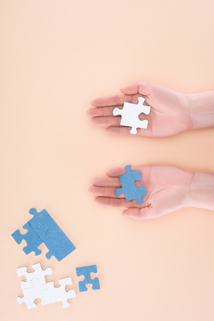 cropped image of businesswoman holding blue and white puzzles in hands isolated on beige, business concept