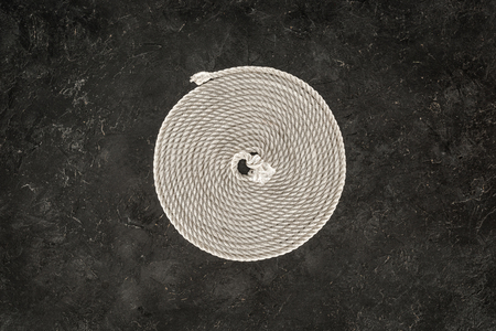 top view of white nautical rope arranged in circle on dark concrete tabletop