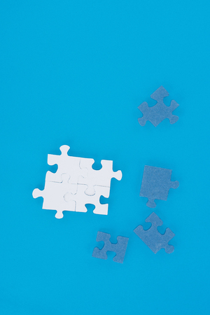 top view of white and blue puzzles isolated on blue, business concept