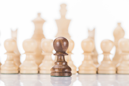 black chess pawn in front of white figures on white