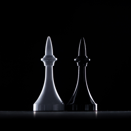 silhouettes of white and black chess bishops isolated on black, business concept