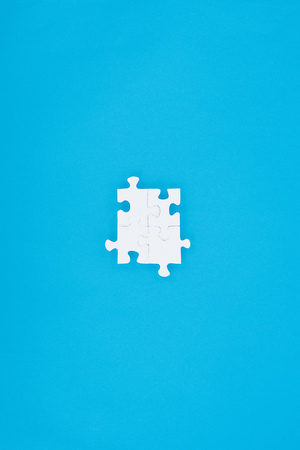 top view of assembled white puzzles isolated on blue, business concept Фото со стока