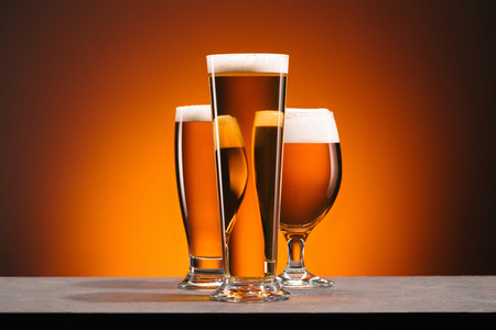 close up view of arrangement of glasses of beer on orange backdrop