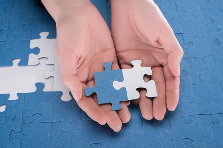 cropped image of businesswoman holding assembled white and blue puzzles, business concept