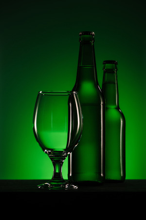 close up view of bottles of beer and empty glass on green background