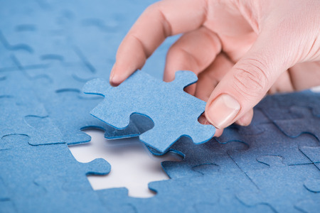 cropped image of businesswoman inserting last missing puzzle, business concept Фото со стока