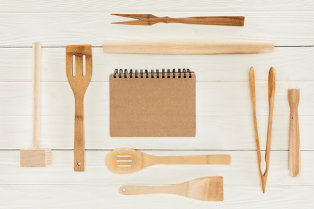top view of textbook and wooden kitchen utensils on white table  스톡 콘텐츠