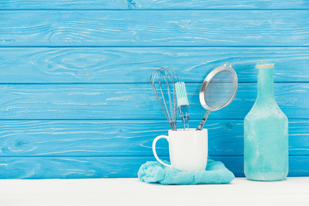 closeup view of rag, whisk, sieve, pastry brush and bottle in front of wooden wall Archivio Fotografico - 101308847