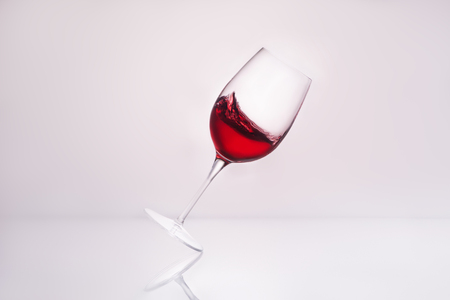 inclined wineglass with splashing red wine on reflective surface and on white Stock Photo